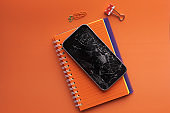 top view of broken smart phone on orange background