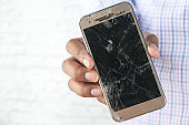 man holding smartphone with a broken screen