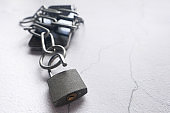 Smart Phone With Padlock And Chain Over White Background.
