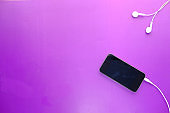 smart phone and earphone on purple background