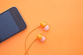 smart phone and earphone on orange background