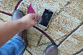 man hand picking broken smart phone from floor