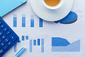 close up of financial charts, calculator and tea on table