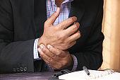 Businessman suffering wrist while woking on desk