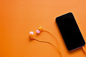 top view of smart phone and headphone on orange background