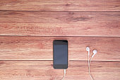 smart phone and earphone on wooden background