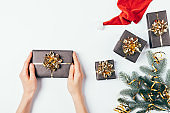 Christmas flat lay composition female hands holding a gift box