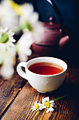 Cup of red tea and two chamomile flowers