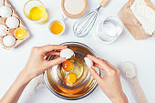 View from above woman's hands crack an egg in bowl to prepare homemade pastry