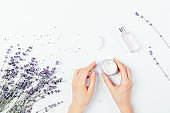 Female hands apply cosmetic cream next to bunch of lavender