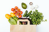 Paper grocery bag full of organic vegetables and greens