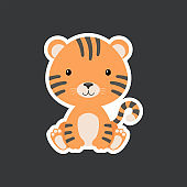 Sticker of cute baby tiger sitting. Adorable jungle animal character for design of album, scrapbook, card, poster, invitation.