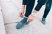 Close-up of young woman tying shoelaces on her sneakers