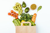 Top view paper grocery shopping bag with healthy food fresh vegetables