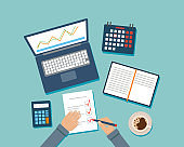 Top View Vector Illustration In Cartoon Flat Style On Blue Background. Desktop With Different Office Items. Hands Of Businessman Writing On Paper, Calculator, Calendar, Planner, Coffee And Laptop Near