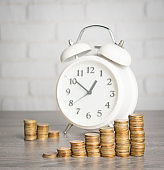 Finance and Money concept,Alarm clock and money coins stack on wood table against white brick wall