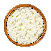 Cottage cheese, curds and whey in a wooden bowl