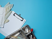 Blank medical clipboard with syringes with needles for vaccination in stainless steel surgical tray