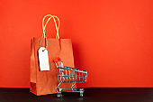 Shopping lover concept : Red paper shopping bags and small toy shopping cart on red background.