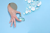 A woman's hand looks out of the hole and holds a bottle of perfume