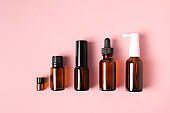 Essential oils , various bottles aromatherapy on a pink background.