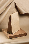 Paper bag and pizza box made of cardboard on a background of craft paper.