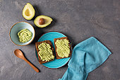 Avocado toasts on whole grain bread, mashed avocado with lime, healthy eating concept, top view