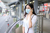 A young woman is wearing face mask in the Street city .