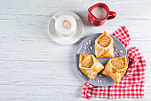 Sweet pastries in the shape of an envelope with heart filled with apples, dessert with cappuccino, top view