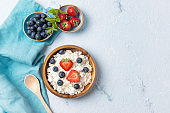 Cottage cheese with strawberry and blueberry, fresh ripe berries and mint leaves, healthy breakfast concept, top view