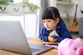A little cute girl is using laptop for studying online via internet at home. E-learning Concept during quarantine time.
