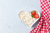 Cottage cheese with fresh strawberry and mint leaves in a heart shaped bowl, fresh berries, healthy breakfast concept, top view