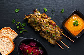 Asian food concept  homemade beef satay grilled and spicy peanut spice sauce  on black slate board with copy space