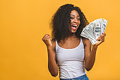 Happy winner. Portrait of african american successful woman 20s with afro hairstyle holding lots of money dollar banknotes isolated over yellow background.