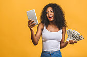 Happy winner. Portrait of african american successful woman 20s with afro hairstyle holding lots of money dollar banknotes and using tablet  isolated over yellow background.
