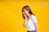 Portrait young happy asian woman smile laughing hand covering your mouth standing enjoy fun relaxing carefree positive emotion in white t-shirt, Yellow background isolated studio shot and copy space.