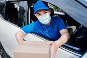 Asian Delivery man wearing mask picking up the package to front home receiver shipping deliver cargo social distancing, Many parcel in car while the virus is spreading quarantine.