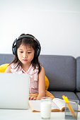 Asian girl using laptop for online study during homeschooling at home