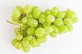 One bunch of ripe organic white grapes isolated on white background, side view with soft focus of tasty healthy food
