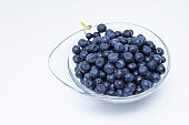 Small transparent bowl with a handle of fresh blueberries on a white background.