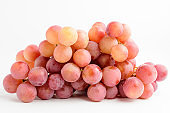 One bunch of ripe organic red pink grapes isolated on white background, side view with soft focus of tasty healthy food