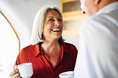 Senior woman enjoying coffee and conversation with husband at home