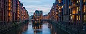 Hamburg warm lamplight illuminating Speicherstadt warehouses canal sunset panorama Germany