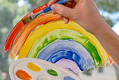 Hand of white woman painting with brush rainbow