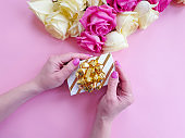 female hands holding a gift box, a bouquet of roses on a colored background
