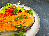 fried salmon slice on a plate, tomato on concrete background