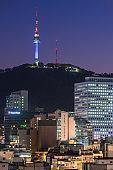 Seoul Namsam Tower illuminated at sunset overlooking downtown cityscape Korea