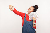 Portrait of joyfully rich stylish girl with hair bun in denim overalls holding money and taking selfie by mobile phone