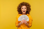Portrait of amazed joyful curly-haired woman in urban style hoodie rejoicing luck in lottery, showing dollars
