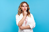 Serious thinking. Portrait of pensive woman touching her chin and considering idea, deep in thoughts. blue background